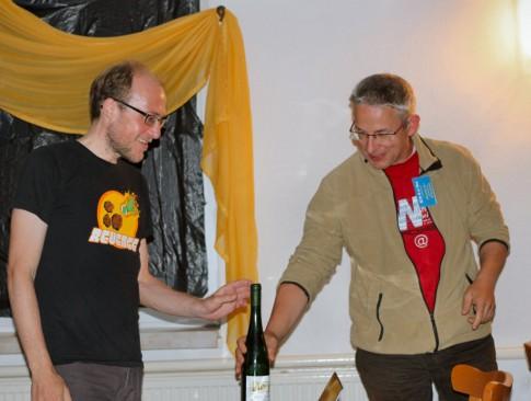 Dirk Landrock vom AstroTeam Elbe-Elster überreicht Florian Freistetter nach seinem Vortrag regionalen Wein